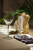 The restaurant served table with wine glass and set of fork and knife. The restaurant served table for one person the sun with wine glass, cloth, paper napkins Royalty Free Stock Photography