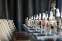 Restaurant serving and glass wine and water glasses, forks and knives on textile napkins stand in a row on a gray wooden table. C royalty free stock photography