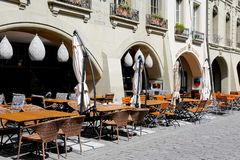 Restaurant on a sidewalk in the Old Town. Bern, Switzerland - April 20, 2017: Outdoor seating restaurant is located next to the arcades of the historical Royalty Free Stock Photo