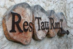 Restaurant sign. Side view rustic old looking restaurant sign in wood Royalty Free Stock Image