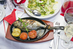 Restaurant Snapshot style photo. Delicious fish of a dolphin is baked on coals with a lemon and tomatoes. Soft focus in combination with sharp lighting Royalty Free Stock Images