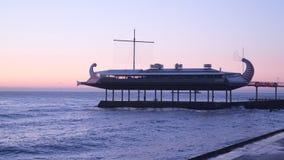 Restaurant sous la forme d'un bateau en mer près du rivage banque de vidéos