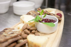 Restaurant Style Cheese and Cracker Platter. A selection of artisan cheeses and crackers served with ripe fresh fruit and preserves, as it would be in a Royalty Free Stock Photo