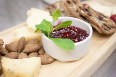 Restaurant Style Cheese and Cracker Platter. A selection of artisan cheeses and crackers served with ripe fresh fruit and preserves, as it would be in a Royalty Free Stock Images