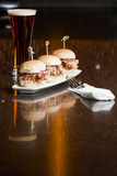 Restaurant Style Plating of Appetizer. A restaurant style presentation of a tall glass of beer and mini slider sandwiches of pulled pork Stock Photos