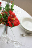 Restaurant table. Wit dishes, flowers and cutlery Royalty Free Stock Photography