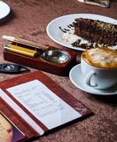 Restaurant table. Check, ashtray, cigar, lighter and coffee at restaurant table royalty free stock photo