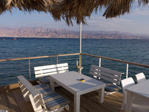 Restaurant table at the beach. Well placed restaurant table with superb view of the blue sea and deserted mountains on the other side. Palapa umbrella keeps the Royalty Free Stock Photo