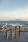 Restaurant table and chairs with a relaxing view of Samothraki i Stock Photo