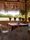 Restaurant table in an echo environment. Out in the wilderness with palapa roof this small and cozy restaurant has no windows. No need for windows as it is Royalty Free Stock Image