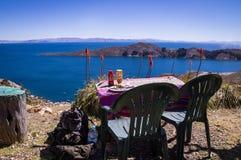 Restaurant table at Isla del Sol, Lake Titicaca, Bolivia. Lunch at Isla de Sol, Bolivia: Restaurant table and chair with view over Lake Titicaca. Isla de Sol was Stock Photos