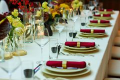 Restaurant table with napkins and wine glasses. Restaurant table with plates and napkins and wine glasses decorated with flowers stock photography