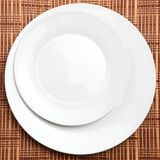 Restaurant Table Placement. Two white plates or dishes photographed over a wooden placement background. Suitable for restaurant or other food-related projects Stock Image