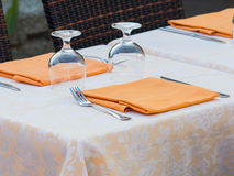 Restaurant table prepared with damask  table cloth orange napkin Royalty Free Stock Images