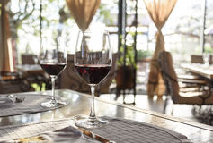 Restaurant table with red wine glasses. Fancy restaurant interior and served table with two glass of red wine royalty free stock image