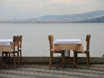 Restaurant table and the sea and city skyline. Royalty Free Stock Photography