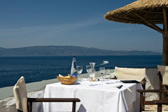 Restaurant table on the seashore. Table with tablecloth and glasses and bottle on it at the seashore royalty free stock image