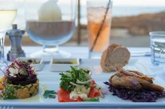 Restaurant table with served entree plate with small snacks. Al fresco fine dining settings with water view royalty free stock images