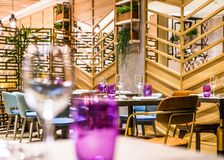 Restaurant table set up for casual dining meal. Wooden restaurant table and leather chairs set up for casual dining meal with natural light flower wall and stock images