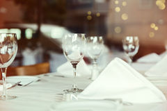 Restaurant table setting with wine glass. Selective focus on wine glass Royalty Free Stock Images