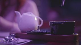 Restaurant table with table settings. In wooden base are teapot and black small bowl where hand put slice of champignon. Mashroom with tweezer. Body of sitting stock footage