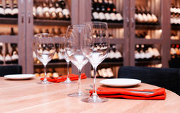 Restaurant table with wine fridge in the background, toned. Restaurant table with wine cellar in blurred background, toned image Royalty Free Stock Photos