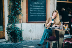 Restaurant table young woman drinking coffee blackboard background Stock Photos