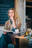 Restaurant table young woman thinking doubt coffee newspaper Royalty Free Stock Photos