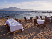 Restaurant tables at the beach. Set restaurant tables with white tablecloth at a beach in Lumio near Calvi, Corsica Royalty Free Stock Images