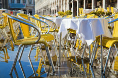 Restaurant tables and chairs at flood in Venice Royalty Free Stock Image