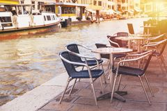 Restaurant tables and chairs with vaporetto ships in the background in Venice, Italy. European travel, outdoor dining and cuisine. Stock Images