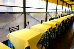 Restaurant Tables Chairs Yellow Tablecloth. Restaurant tables and chairs with clear yellow tableclothes in a row Stock Image