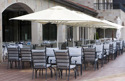 Restaurant tables chares umbrellas. Restaurant tables, chairs and white umbrellas Royalty Free Stock Photo