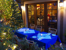 Restaurant tables in Christmas lighting. Two tables set in the restaurant patio with blue and white table cloths waiting for diners. Large window showing the the Stock Images