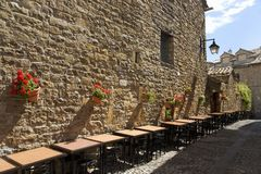 Restaurant tables at Plaza Mayor, in Ainsa, Huesca, Spain in Pyrenees Mountains, an old walled town with hilltop views of Cinca an Royalty Free Stock Photography