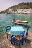 Restaurant tables by the sea in the scenic village of Loutro  in Crete Greece. Restaurant tables by the sea in the scenic village of Loutro  in Crete, Greece Stock Image