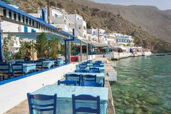 Restaurant tables by the sea in the scenic village of Loutro  in Crete Greece. Restaurant tables by the sea in the scenic village of Loutro  in Crete, Greece Stock Photo