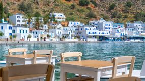 Restaurant tables with view on the scenic village of Loutro  in Crete Greece. Restaurant tables with view on the scenic village of Loutro  in Crete, Greece Royalty Free Stock Photos