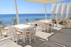 Restaurant - tavern by the sea. Typical greek tavern - cafe on balcony, by the Aegean sea Royalty Free Stock Image