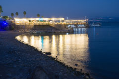 Restaurant in Tiberias. TIBERIAS, ISRAEL - OCT 02, 2014: Ligths from a restaurant are reflecting in the water of the Lake of Galilee on the coast of Tiberias Stock Images