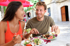 Restaurant tourists couple eating at outdoor cafe. Summer travel people eating healthy food together at lunch during holidays in Mallorca, Spain. Asian Royalty Free Stock Image