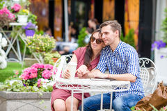 Restaurant tourists couple eating at outdoor cafe. Young woman enjoy time with her husband, while man reading. Happy couple enjoying sitting in outdoor cafe royalty free stock photo