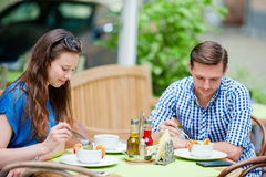 Restaurant tourists couple eating at outdoor cafe. Young woman and her friend enjoy their food at lunch time Royalty Free Stock Photos