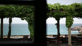 The restaurant at the Villa Milocer, under the wisteria trees, t. He park and the beach of the Queen, near the island of Sveti Stefan, Montenegro stock footage