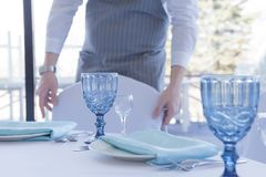 Restaurant the waiter serves a table for a wedding celebration, moves a chair royalty free stock photography