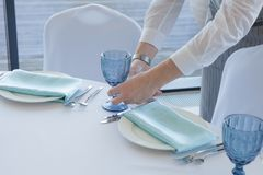 Restaurant waiter serves a table for a wedding celebration royalty free stock photo