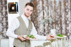 Restaurant waiter serving plates with food Royalty Free Stock Photos