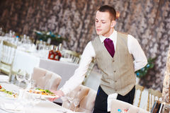Restaurant waiter serving table with food Royalty Free Stock Photos