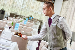 Restaurant waiter serving table with food Stock Photo