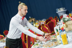 Restaurant waiter serving table with food Stock Images